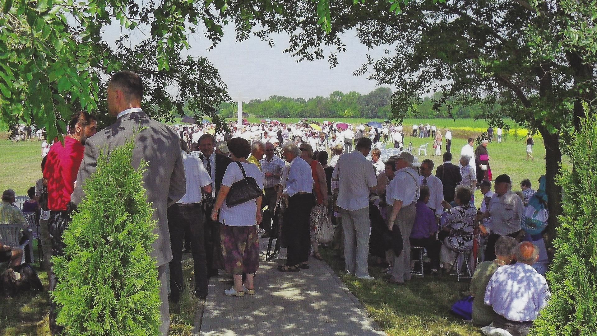 Die angereiste Gedenkgemeinde versammelt sich im Schatten der Bäume und um das Kreuz. Es sind ca. 600 Personen angereist. Foto: Kupferschmidt