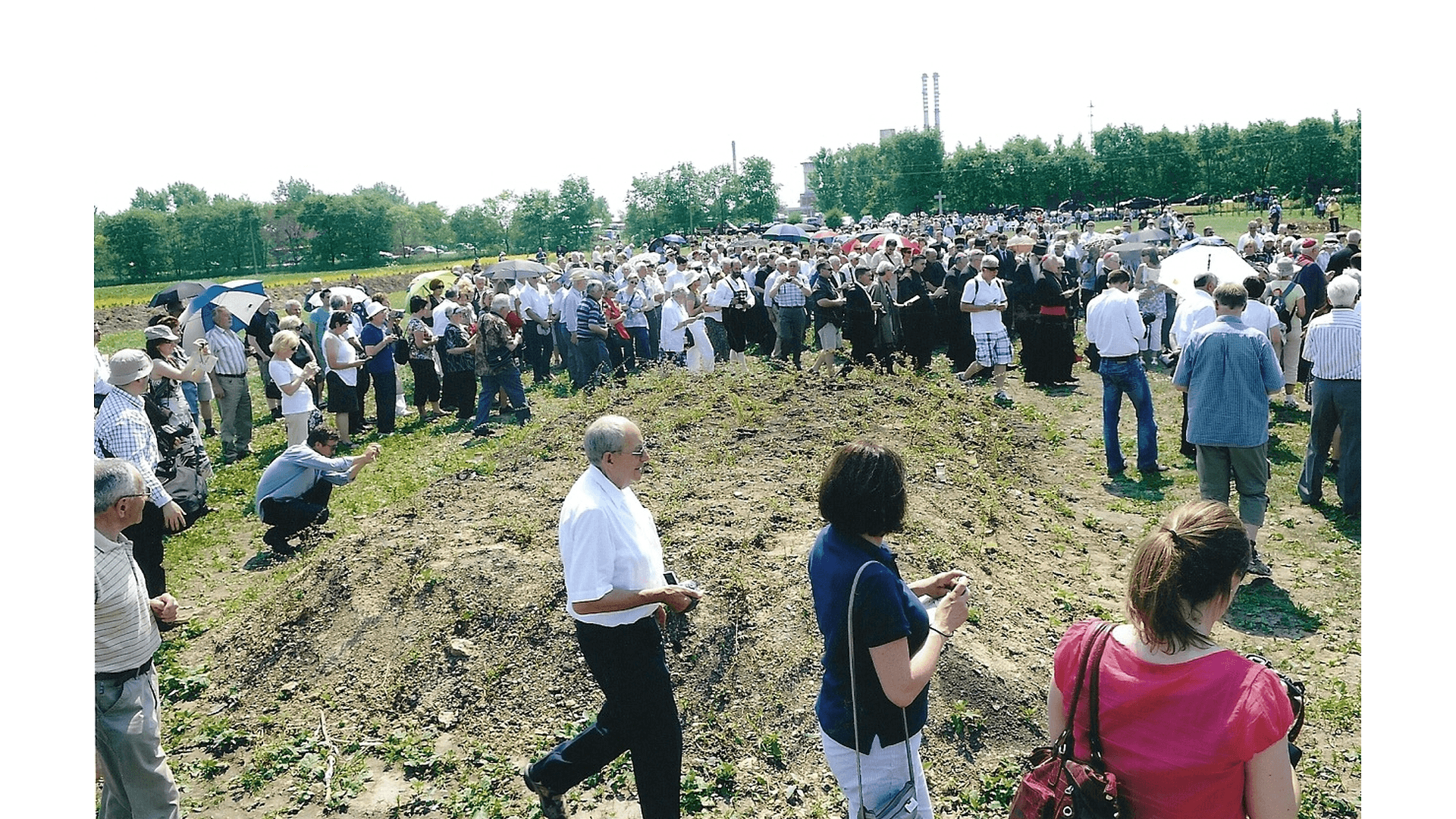 Die Prozession erreicht das größte Massengrab in dem laut späteren Berichten von am Massaker unbeteiligten Partisanen ca. 180 Tote ruhen. Auf die zwei kleineren Gräber verteilt sich der Rest der Opfer welche nach dem Zuschütten des großen Grabes ermordet wurden.